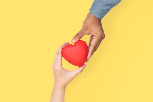 Mani che tengono il cuore nell'amore e nel concetto di relazione