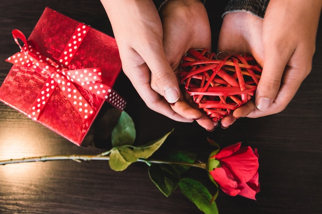 Hands holding a heart with a gift and a rose