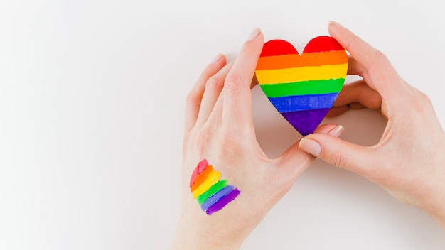 Hands holding a heart with pride day flag colors