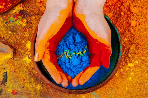 Hands holding holi powder paint, view from above