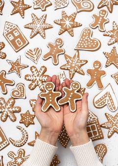 自家製の2つのジンジャーブレッドマンクッキーを持っている手。クリスマスの甘い食べ物のコンセプト。上面図。