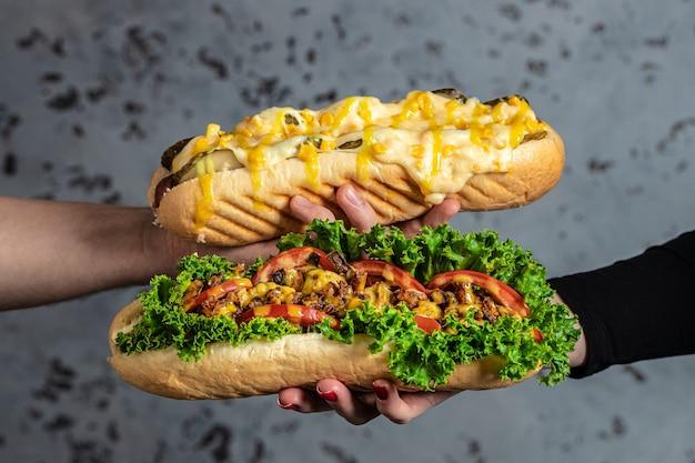 Руки держат хот-доги, полностью загруженные разными начинками. хот-дог быстрого питания, американская нездоровая калорийная еда. баннер, меню, рецепт место для текста