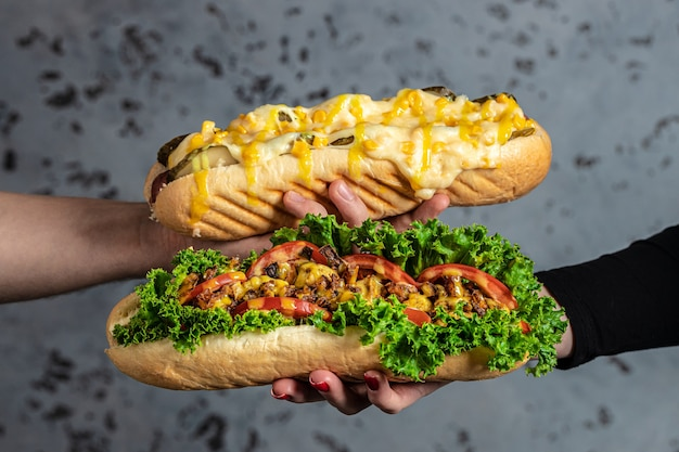各種トッピングがたっぷり詰まったホットドッグを手に。ファーストフードのホットドッグ、アメリカの不健康なカロリーの食事。バナー、メニュー、テキストのレシピの場所