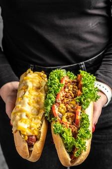 各種トッピングがたっぷり詰まったホットドッグを手に。ファーストフードのホットドッグ、アメリカの不健康なカロリーの食事。垂直方向の画像。上面図。テキストの場所