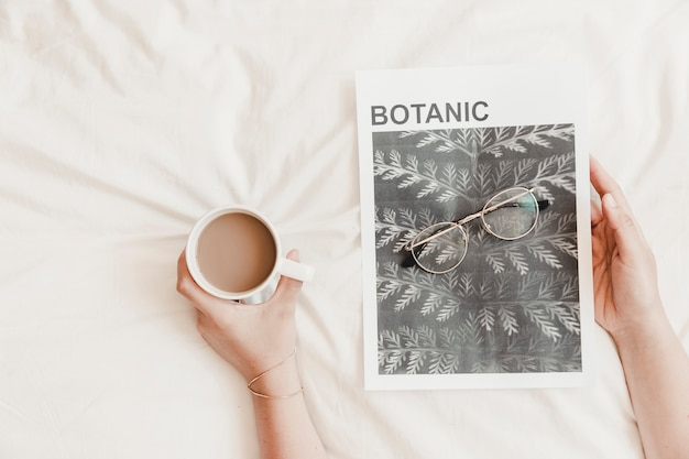Hands holding hot drink and poster with eyeglasses on bedsheet