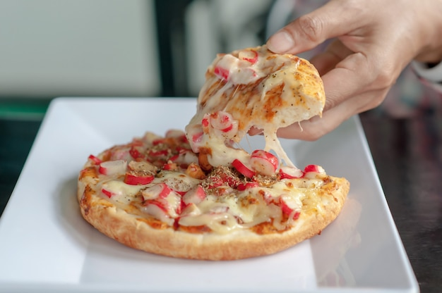 Hands holding hot pizza in restaurant