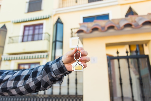 Hands holding house keys on house shaped keychain in front of a new home.
