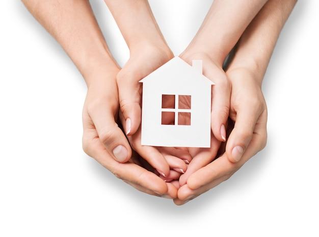 白で隔離の家のモデルを保持している手