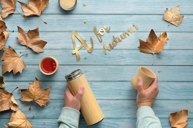 Hands holding insulated metal flask and bamboo cup. eco-friendly tea in fall. flat lay on faded light wood  autumn leaves.