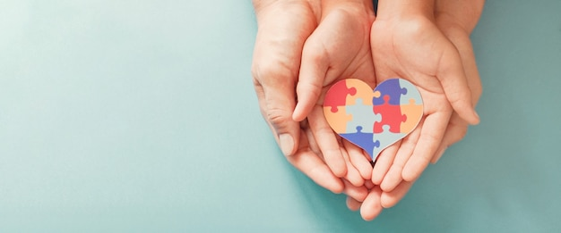 Hands holding jigsaw puzzle heart shape, world autism awareness day