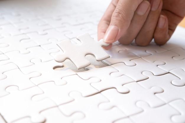 직소 퍼즐을 손에 들고. 사업 제휴 및 팀워크 개념.