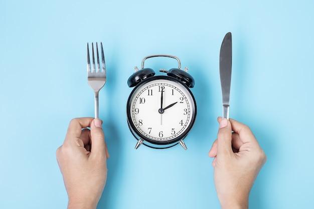 파란색 배경에 흰색 접시에 알람 시계 위에 나이프와 포크를 들고 손. 간헐적 단식, 케토제닉 다이어트, 체중 감량, 식사 계획 및 건강 식품 개념