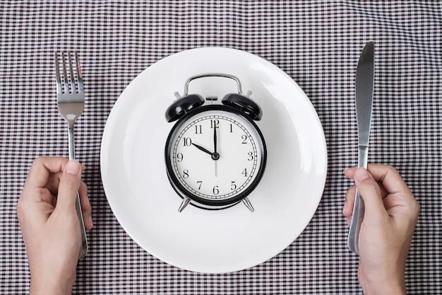 식탁보 배경에 흰색 접시에 알람 시계 위에 나이프와 포크를 들고 손. 간헐적 단식, 케토제닉 다이어트, 체중 감량, 식사 계획 및 건강 식품 개념