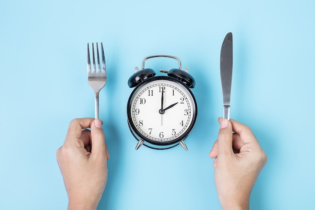Hands holding knife and fork above alarm clock on white plate on blue background. intermittent fasting, ketogenic dieting, weight loss, meal plan and healthy food concept