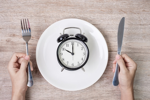Hands holding knife and fork above alarm clock on white plate on wooden table background.