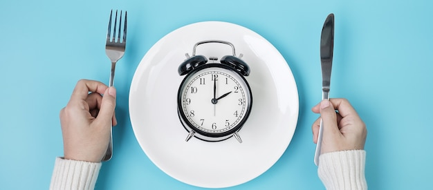 Hands holding knife and fork above alarm clock on white plate