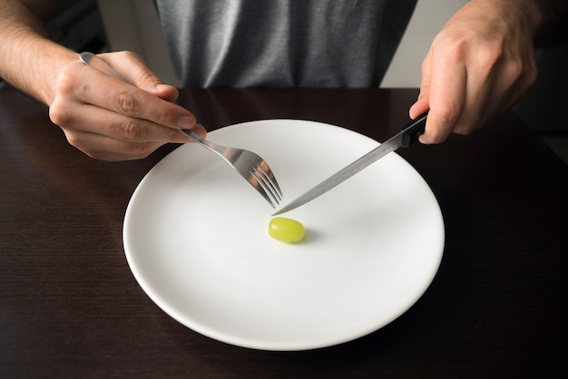 Hands holding knife and fork on a plate with green grape on a white plate