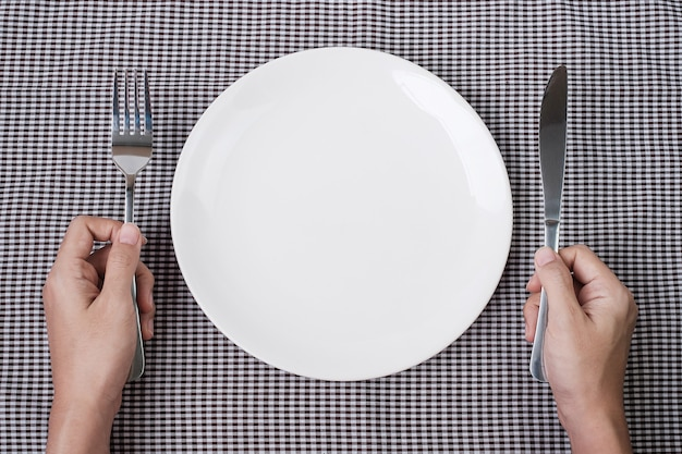 Hands holding knife and fork above white plate on table background