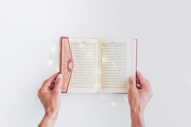 Hands holding koran with lighting garland