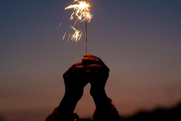 夕日の背景に光を保持している手。新年の目標
