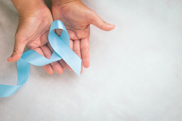 コピースペースのある白い布のテーブルに水色のリボンを持っている手リンパ浮腫と前立腺がんの意識月のシンボルヘルスケア医療と保険の概念男性のがん