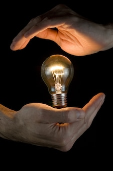 Hands holding a light bulb on a black background