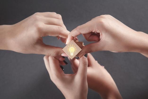 나무 큐브에 전구를 들고 손입니다.