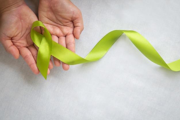 コピースペースと白い布の背景にライトライムグリーンのリボンを保持している手。世界メンタルヘルスデーとリンパ腫啓発のシンボル。