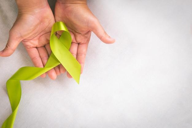 コピースペースのある白い布のテーブルにライトライムグリーンのリボンを持っている手世界メンタルヘルスデーとリンパ腫の意識のシンボルヘルスケア医療と保険の概念