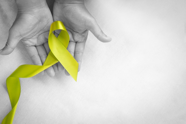 Hands holding light lime green ribbon on white fabric background world mental health day concept