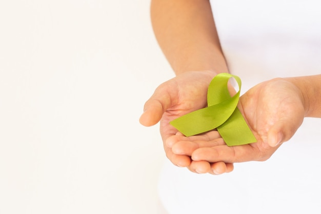 Hands holding light lime green ribbon world mental health day and lymphoma awareness symbol