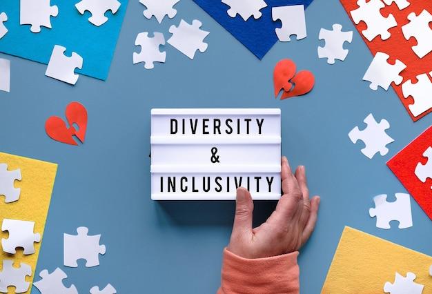 Руки держат лайтбокс с текстом «разнообразие и инклюзивность». плоская планировка, вид сверху на творческую аранжировку.