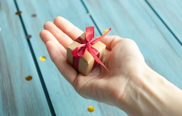 붉은 활과 작은 선물을 들고 손입니다. 확대.