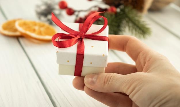 赤い弓で小さな贈り物を持っている手。閉じる。