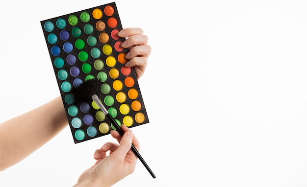 Руки держат кисть для макияжа с палитрой и копией пространства