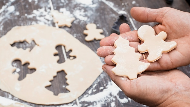 Hands holding man and christmas tree shaped pastry