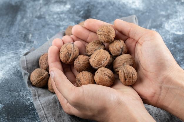 Руки держат много здоровых грецких орехов на мраморной поверхности.