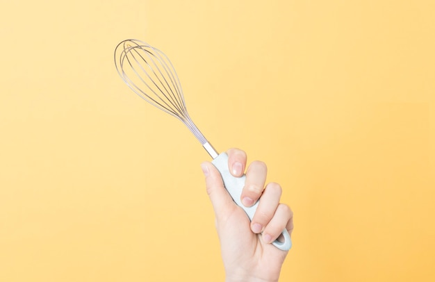 Hands holding a metal whisk on yellow paper background. kitchen tool for whipping cream or eggs.