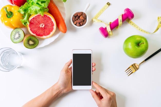 테이블 배경에 휴대 전화를 들고 손입니다. 깨끗한 식사, 다이어트 및 운동 개념