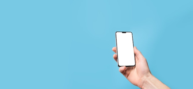 携帯電話、青い背景に白い画面のスマートフォンを持っている手。モックアップ。アプリケーションまたはwebサイトデザインプロジェクトにモックアップを使用できます。テキスト用のスペース。バナー。