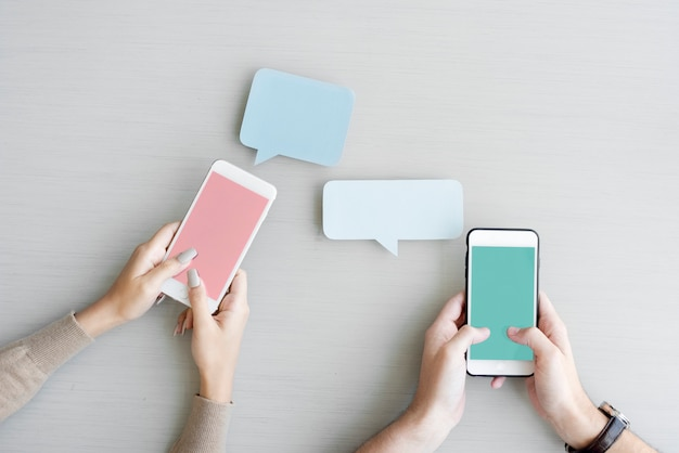 Hands holding mobile phones featuring speech bubbles