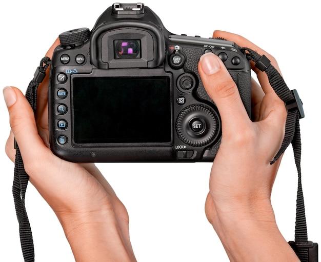 흰색 배경에 고립 된 현대 카메라를 들고 손