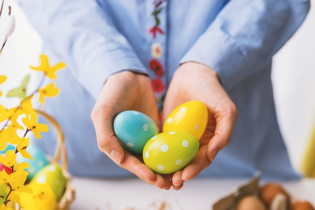 Hands holding modern painted easter eggs.
