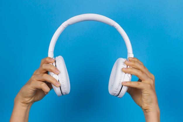 Hands holding modern white wireless headphones on light blue wall