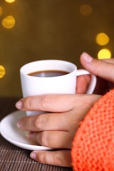 Hands holding mug of hot drink, close-up, on bright background