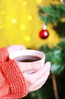 뜨거운 음료의 낯 짝을 들고 손 클로즈업, 크리스마스 트리