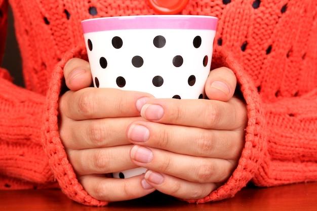 Руки держат кружку горячего напитка крупным планом