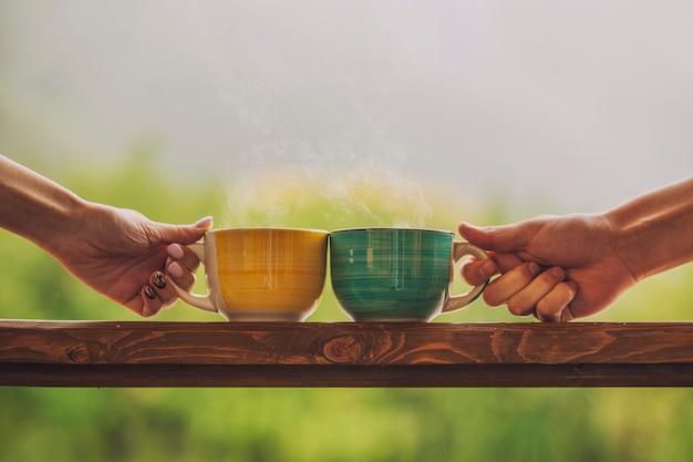 田舎の屋外の木製スタンドにお茶を入れて、温かい飲み物とマグカップを持っている手