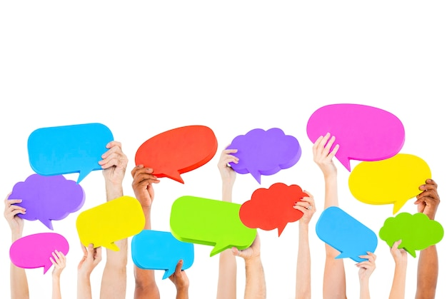 Hands holding multi colored speech bubbles.