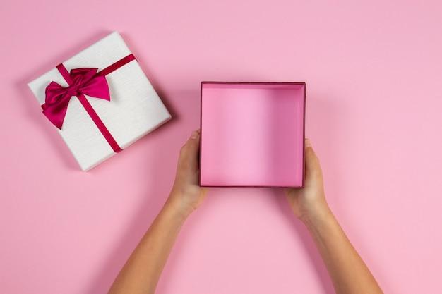 Руки держат открытую пустую подарочную коробку на пастельно-розовом фоне, вид сверху